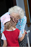 Great grandmother affectionally kissing young girl goodbye age 88 and 5. Zawady Central Poland