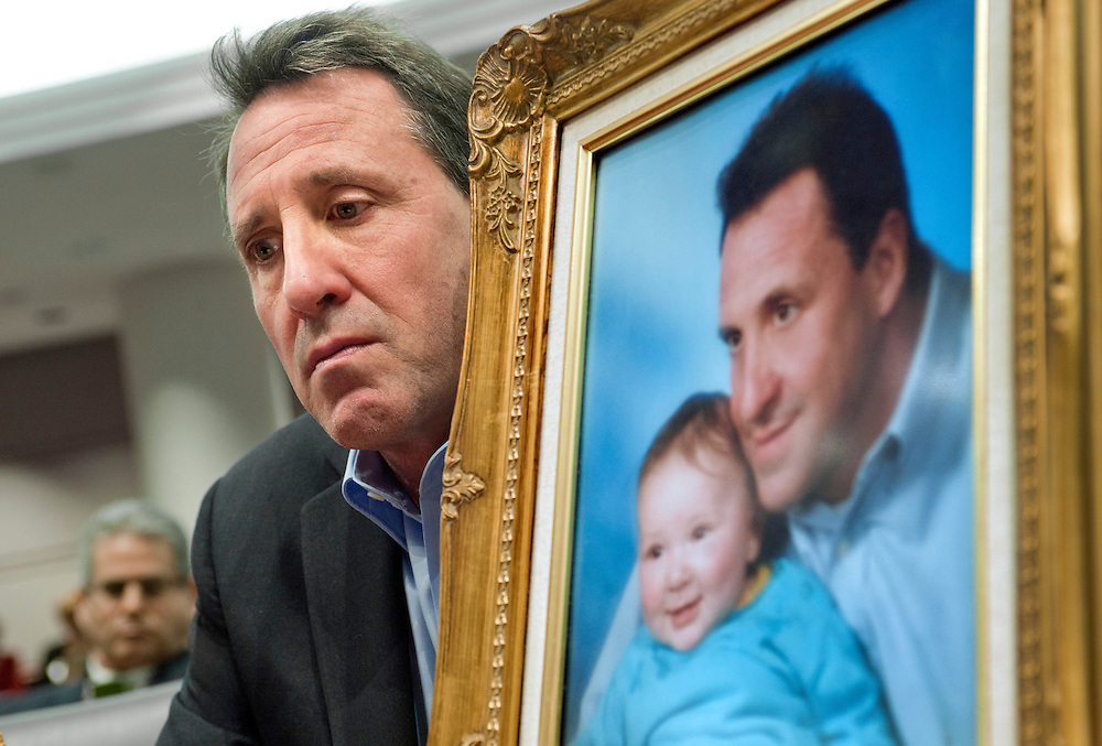Neil Heslin, holding a picture of himself with his son Jesse Lewis, testifies at the Legislative Office Building in Hartford, Conn. Heslin, whose 6-year-old son Jesse Lewis was one of the 20 first-graders killed in the Dec. 14 massacre at Sandy Hook Elementary School in Newtown, Conn. , told a legislative subcommittee reviewing gun laws that there is no need for such weapons in homes or on the streets. (AP Photo/Jessica Hill)