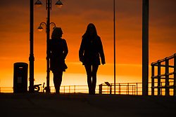© Licensed to London News Pictures.<br /> Aberystwyth UK, 26/03/2019<br />  A beautiful sunset , at the end of another day of warm spring sunshine, silhouettes two women walking along the promenade  in Aberystwyth, on the Cardigan Bay coast of west Wales. High pressure continues to dominate the weather for much of the UK, with settled conditions and clear blue skies<br /> photo Keith Morris/LNP