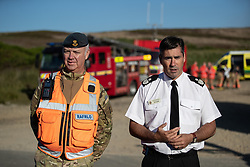 "© Licensed to London News Pictures . 28/06/2018 . Saddleworth , UK . Wing Commander GARY LANE Lane (l), RAF Regional Liaison Officer for the North West and Area Manager TONY HUNTER of Greater Manchester Fire and Rescue host a press conference at Higher Swineshaw Reservoir . The army are being called in to support fire-fighters , who continue to work to contain large wildfires spreading across Saddleworth Moor and affecting people across Manchester and surrounding towns . Very high temperatures , winds and dry peat are hampering efforts to contain the fire , described as "" unprecedented "" by police and reported to be the largest in living memory . Photo credit: Joel Goodman/LNP"