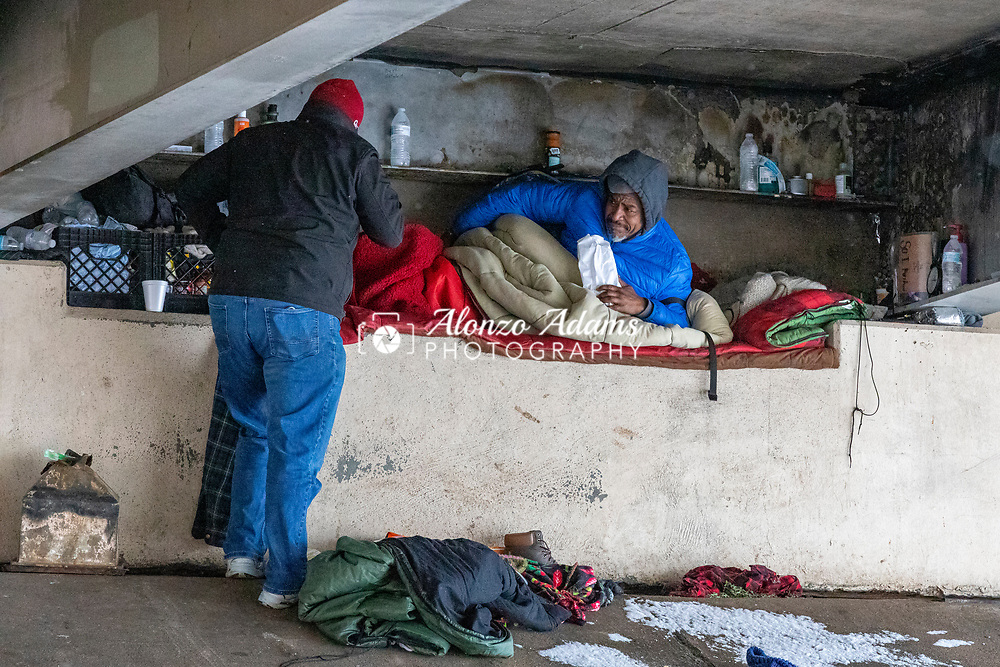 Luke S. with the Salvation Army checks on a homeless man under a bridge during freezing cold temperatures and snow in Oklahoma City on Friday, February 12, 2021. Photo copyright © 2021 Alonzo J. Adams