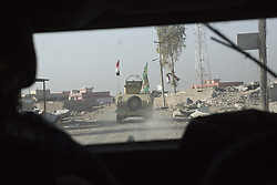 November 11, 2016 - Mosul, Nineveh, Iraq - 11/11/2016. Mosul, Iraq. An Iraqi Army armoured Humvee, belonging to the Iraqi 9th Armoured Division, is seen through bullet proof windscreen as an Iraqi Army convoy travels through a suburb of Mosul, Iraq...The battle to retake Mosul, which fell June 2014, started on the 16th of October 2016 with Iraqi Security Forces eventually reaching the city on the 1st of November. Since then elements of the Iraq Army and Police have succeeded in pushing into the city and retaking several neighbourhoods allowing civilians living there to be evacuated - though many more remain trapped within Mosul...The battle to retake Mosul, which fell June 2014, started on the 16th of October 2016 with Iraqi Security Forces eventually reaching the city on the 1st of November. Since then elements of the Iraq Army and Police have succeeded in pushing into the city and retaking several neighbourhoods allowing civilians living there to be evacuated - though many more remain trapped within Mosul. (Credit Image: © Matt Cetti-Roberts via ZUMA Wire)