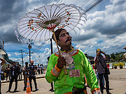 23 JUNE 2016 - MAHACHAI, SAMUT SAKHON, THAILAND:   A man dressed as a traditional Burmese street performer walks through the crowd while waiting for Aung San Suu Kyi to arrive in Samut Sakhon, a province south of Bangkok. Tens of thousands of Burmese migrant workers, most employed in the Thai fishing industry, live in Samut Sakhon. Aung San Suu Kyi, the Foreign Minister and State Counsellor for the government of Myanmar (a role similar to that of Prime Minister or a head of government), is on a state visit to Thailand. Even though she and her party won the 2015 elections by a landslide, she is constitutionally prohibited from becoming the President due to a clause in the constitution as her late husband and children are foreign citizens      PHOTO BY JACK KURTZ