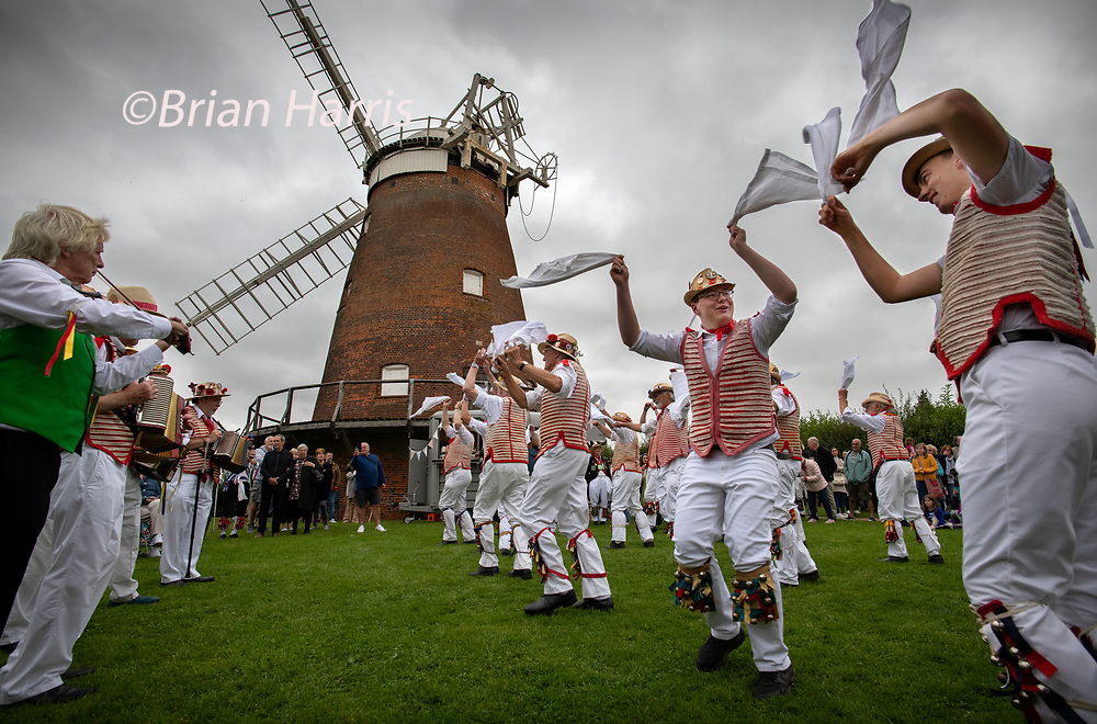Thaxted Essex_Morris Dancing_August Bank Holiday Monday_photo Brian Harris_30 Aug 2021<br />Dancing in the grounds of John Webb's Windmill dating from the early 19th century for the first time ever.<br />Thaxted Morris Men in red and white take the lead in some mass Morris Dancing under a threatening sky.<br />Photograph Brian Harris/Alamy News
