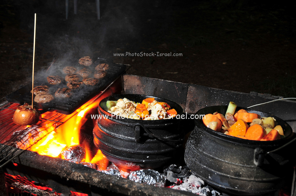 Cooking on an open fire, an iron caldron on an outdoor wood fire