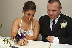 Bride who has cerebral palsy, with groom signing marriage certificate.