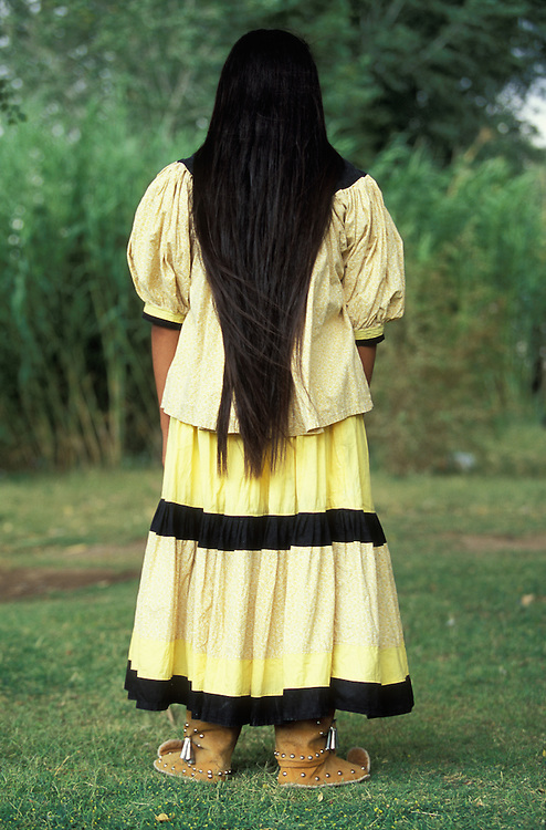 A portrait from behind of an Apache girl with long hair on the San Carlos Apache Indian Reservation in Arizona, USA. June 2004. The girl is dressed in camp dress and moccasins.