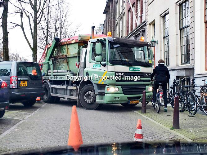 Nederland, Amsterdam, 18-2-2019 Een vrachtwagen van een containerbedrijf moet een vuilcontainer wisselen aan de Keizersgracht. Het duurt even vanwege de krappe ruimte om de manoeuvre te kunnen uitvoeren. De vakkundige chauffeur weet het werk zonder schade te klaren. Het andere verkeer moet wachten, kan er nier door.Foto: Flip Franssen