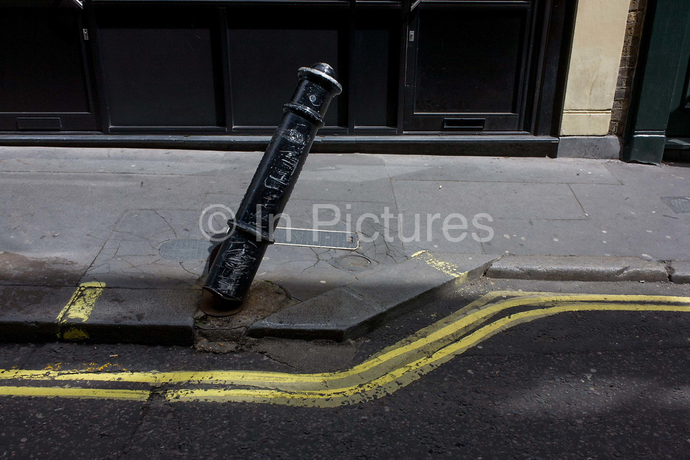Leaning traffic post and twisting double-yellow lines in Soho, central London. We look down to street level to see the wonky character of lines and geometry: The badly-painted parallel parking restrictioin lines that bend with the angle of the kerb as well as the damaged, scraped and leaning bollard, there to deter drivers from parking on the pavement but which has been pushed over by a driver. The picture is about the irony of geometry, of the madness of urban details.