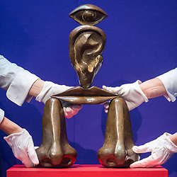"© Licensed to London News Pictures. 20/02/2019. LONDON, UK. Technicians hold ""La Race Blance"", 1967, by René Magritte, (Est. £0.3-0.5m). Preview of Sotheby's Impressionist & Modern and Surrealist Art sales.  The auction will take place at Sotheby's New Bond Street on 26 February 2019.  Photo credit: Stephen Chung/LNP"