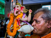 "23 SEPTEMBER 2018 - BANGKOK, THAILAND: A man blows a prayer conch to honor Ganesha at the Ganesha Festival at Wat Dan in Bangkok. Ganesha Chaturthi also known as Vinayaka Chaturthi, is the Hindu festival celebrated on the day of the re-birth of Lord Ganesha, the son of Shiva and Parvati. The festival, also known as Ganeshotsav (""festival of Ganesha"") is observed in the Hindu calendar month of Bhaadrapada, starting on the the fourth day of the waxing moon. The festival lasts for 10 days, ending on the fourteenth day of the waxing moon. Outside India, it is celebrated widely in Nepal and by Hindus in the United States, Canada, Mauritius, Singapore, Thailand, Cambodia, and Burma.    PHOTO BY JACK KURTZ"