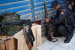 Um policial do BOPE segura uma metralhadora antiaérea calibre 1:50 apreendida com  os traficantes na favela Morro do Alemão em 28 novembro de 2010 no Rio de Janeiro, Brasil. Após dias de preparação, forças de segurança do Brasil, lançaram um ataque contra uma favela, onde entre 500 e 600 traficantes de drogas estão escondidos e se recusam a se render. Cerca de 2.600 tropas aerotransportadas, marines e membros das unidades de elite da polícia faziam parte na operação como alvo um grupo de favelas sem lei, conhecido como Complexo de Alemào. A operação já matou 35 pessoas. FOTO: Jefferson Bernardes/Preview.com