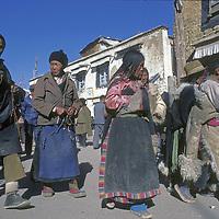 CHINA, TIBET. Tibetan Buddhist pilgrims circle Jokhang Temple through Lhasa's Barkhor Bazaar in 1986.