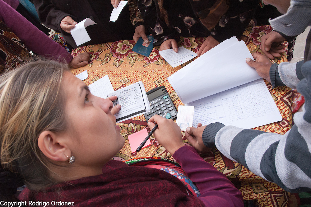 Save the Children staff check the documents and verify the identity of beneficiaries during a distribution of food donated by the World Food Programme (WFP) in the neighborhood of Kizil Kishtak in Osh, Kyrgyzstan.