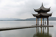 A man stands in a pavilion on the waterfront of West Lake in Hangzhou, China, on Monday, Sept. 5, 2016. The lake, a popular and crowded tourist destination, saw a rare quiet day as the government shut the area down for tourists and residents alike for the G20 meeting held in the city, returning the lake to its serenity of the old days.
