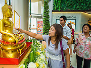 "10 APRIL 2014 - BANGKOK, THAILAND:  A Thai Buddhist bathes a Buddha statue at Siam Paragon, an upscale mall in Bangkok, for Songkran. Many malls put out shrines for Songkran so people can pray and make merit while they shop. Songkran, also called the ""Water Festival"" is the traditional Thai New Year. It was celebrated as the New Year until 1940, when Thailand made January 1 the official start of the New Year. Songkran is now a three day holiday starting on April 13. Many people go to temples to make merit in the days leading up to Songkran. They bathe Buddha statues to bring themselves good luck in the coming year. The holiday is best known for water fights and throwing water at strangers. Thais and foreigners go out with giant squirt guns or buckets of water and throw the water at strangers.   PHOTO BY JACK KURTZ"