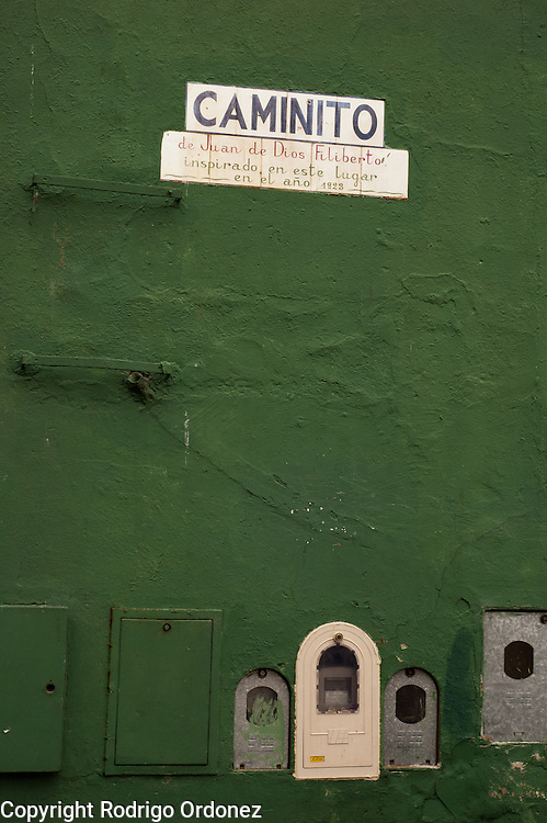 A sign indicates that the tango song 'Caminito' was inspired by this place, Caminito street, in La Boca neighborhood of Buenos Aires, Argentina.<br /> Caminito is a pedestrian street created in the late 1950s by local painter Benito Quinquela Martín and other artist friends to recreate a version of the old immigrant neighborhood of La Boca, using wood and corrugated zinc painted in bright colors. Today, Caminito and the surrounding areas feature cafes, souvenir shops, tango dancers and other street performances aimed to attract tourists.