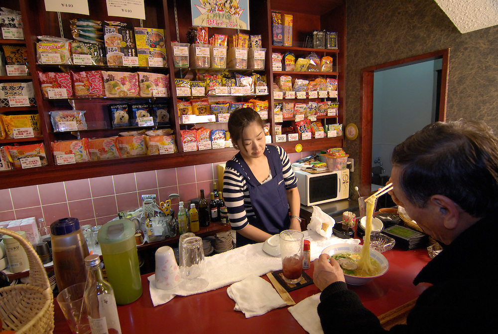 A customer at Sakura instant ramen restaurant samples one of 200 varieties of instant ramen. Staff member Chie Tanaka works behind the bar. Owner Sakura Takenaka founded the restaurant 2 years ago and now has 10 franchises over Japan.