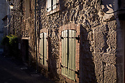 Closed wooden shutters in the late sunshine in pretty French medieval walled village of Lagrasse on the River Orbieu, on 23rd May, 2017, in Lagrasse, Languedoc-Rousillon, south of France. Lagrasse is listed as one of Frances most beautiful villages and lies on the famous Route 20 wine route in the Basses-Corbieres region dating to the 13th century.