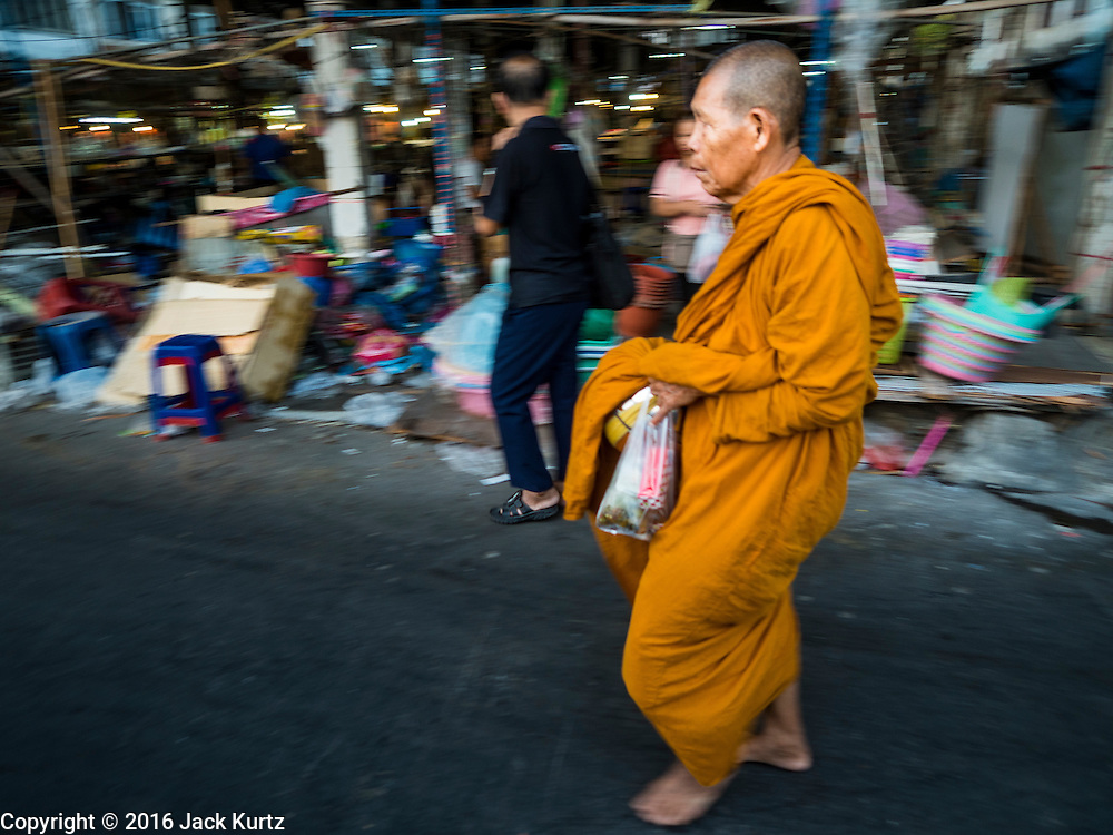 04 JANUARY 2016 - BANGKOK, THAILAND:         A Buddhist monk walks past Bang Chak Market on the last day it was open. The market closed January 4, 2016. The Bang Chak Market serves the community around Sois 91-97 on Sukhumvit Road in the Bangkok suburbs. About half of the market has been torn down. Bangkok city authorities put up notices in late November that the market would be closed by January 1, 2016 and redevelopment would start shortly after that. Market vendors said condominiums are being built on the land.     PHOTO BY JACK KURTZ