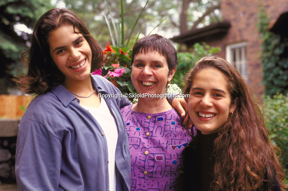 Tongan American daughters age 15 and 16 embracing mom age 48.  St Paul Minnesota USA