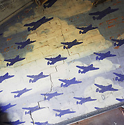 In a farmer's tool shed, a painted mural depicting B-24 Liberators sweeping over the cracked brick wall of what was once an officers' mess at the WW2 Wendling airfield, Norfolk England. Below this scene of heroic military might, young officers flying Liberators of the 392nd Bomb Group gathered before and after raids into Germany from November 1943 to July 1945. The runway is now partly covered by a turkey farm and this building is now full of car and tractor parts. Picture from the 'Plane Pictures' project, a celebration of aviation aesthetics and flying culture, 100 years after the Wright brothers first 12 seconds/120 feet powered flight at Kitty Hawk,1903.