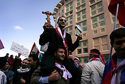 A demonstrator shows the unity of the Lebanese people in their anger against Syria by holding a cross and the Koran, Beirut, Lebanon, Feb. 21, 2005. Several thousand Lebanese gathered at the scene of the bombing that killed former Prime Minister Rafik Hariri, afterward they walked to his grave.