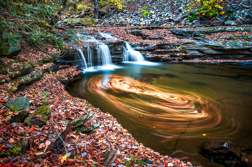A long exposure shows the pattern of leaves swirling on the surface of this small pool that sits below a waterfall near the trailhead at the top of Glade Creek in the New River Gorge, West Virginia.