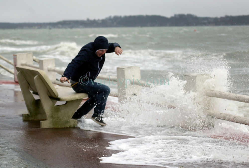 13 Jan 2017. Le Crotoy, Picardie, France.<br /> Gaetan Quenot jumps from a bench as the sea surges toward him as a fierce winter storm pushes the tide over the surge barrier on the Promenade Jules Noiret in the Bai Somme.<br /> Photo©; Charlie Varley/varleypix.com