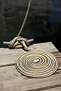 Neat coil of nautical rope on a dock attached to a cleat