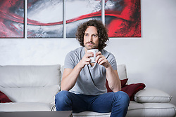 Man sitting on couch and drinking cup of coffee, Munich, Bavaria, Germany