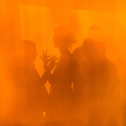 A woman and man play hand shadow puppet on a colorful orange wall.