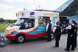London, UK. 5th June, 2021. Police officers queue for an ice-cream van in front of the Royal Docks at Silvertown. It was a warm, dry and mainly sunny day in London due to a ridge of high pressure across the UK from the south west.
