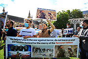 Afghani interpreters holding banners and placards outside Westminster Palace, Houses of Parliament in central London on Wednesday, Aug 18, 2021 - are protesting to call upon the British government and Northern armed allies to not abandon Afghanis who served foreign troops during 20 years of occupation. (VX Photo/ Vudi Xhymshiti)