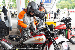 Cris Sommer-Simmons fills her bike on a fuel stop during the Cross Country Chase motorcycle endurance run from Sault Sainte Marie, MI to Key West, FL. (for vintage bikes from 1930-1948). Stage 1 from Sault Sainte Marie to Ludington, MI USA. Friday, September 6, 2019. Photography ©2019 Michael Lichter.
