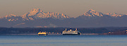 The Olympic mountains reflect red sunrise light as Edmonds Kingston ferries pass each other early in the morning. (Mike Siegel / The Seattle Times)