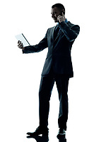 one caucasian business man standing using digital tablet and telephone silhouette isolated on white background