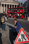 A man next to a Man At Work traffic sign, stands up after crouching on the bust street on 8th September 2016, in the City of London, England UK. In the background are the pillars of Royal Exchange. It is rush hour and commuters are beginning their journeys home from the heart of the capitals financial district, founded by the Romans in the first century.