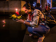 25 NOVEMBER 2015 - BANGKOK, THAILAND: A woman prays before floating her krathong in a khlong (canal) during Loy Krathong near Wat Yannawa in Bangkok. Loy Krathong takes place on the evening of the full moon of the 12th month in the traditional Thai lunar calendar. In the western calendar this usually falls in November. Loy means 'to float', while krathong refers to the usually lotus-shaped container which floats on the water. Traditional krathongs are made of the layers of the trunk of a banana tree or a spider lily plant. Now, many people use krathongs of baked bread which disintegrate in the water and feed the fish. A krathong is decorated with elaborately folded banana leaves, incense sticks, and a candle. A small coin is sometimes included as an offering to the river spirits. On the night of the full moon, Thais launch their krathong on a river, canal or a pond, making a wish as they do so.     PHOTO BY JACK KURTZ