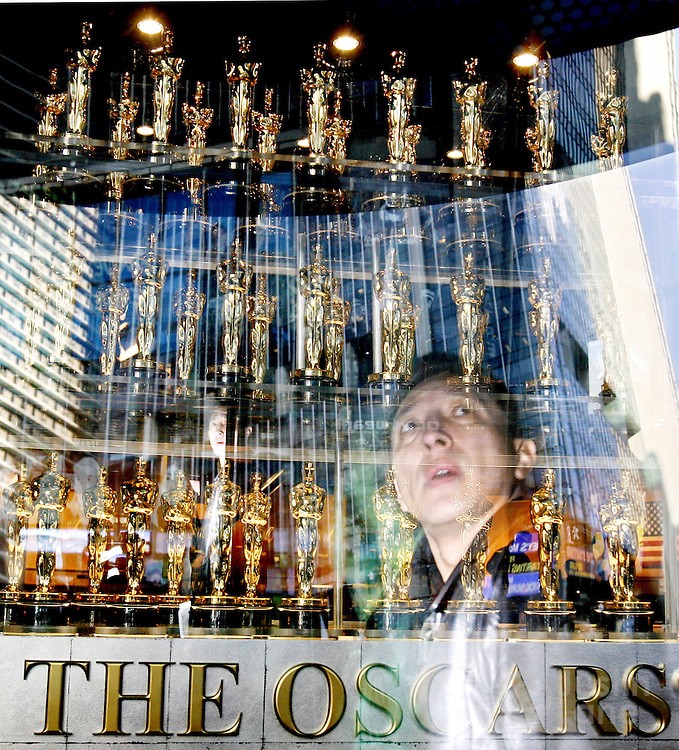 epa00622098 Two passersby look over the 50 official Oscar statuettes on display in Times Square in New York Tuesday 24 January 2006. This is the first time the statuettes have been displayed in New York, a event meant to promote the Academy Awards, which are being held 5 March 2006 in Los Angeles.  EPA/JUSTIN LANE