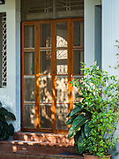"""05 NOVEMBER 2015 - YANGON, MYANMAR: The front door to the home of Aung San Suu Kyi. She lived in house arrest here for more than 15 years. Suu Kyi is now contesting a national election in Myanmar and hosted a press conference at her home. During the press conference, which lasted 90 minutes, Aung San Suu Kyi, the leader of the National League for Democracy (NLD), said that if the NLD won the election she would serve """"above"""" the President. When questioned about the Rohingya crisis in western Myanmar, a reporter called the situation """"dramatic"""" and Suu Kyi replied the entire country is in a """"dramatic situation"""" and the problems of the Rohingya should not be """"exaggerated."""" She said the """"great majority of our people remain as poor as ever."""" She also said the NLD would make a """"fuss"""" if election results were """"suspicious."""" Citizens of Myanmar go to the polls Sunday November 8 in what is widely viewed as the most democratic and contested election in Myanmar's history. The NLD is widely expected to win the election.   PHOTO BY JACK KURTZ"""