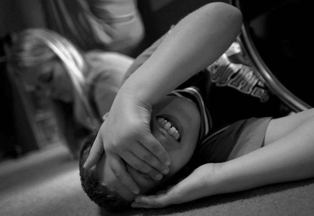 Parker Roos, who suffers from Fragile X, rolls around on the floor after getting into an argument with his sister as his mother Holly looks on at their home in Canton, Illinois, April 4, 2012. Fragile X is the most common known genetic cause of Autism.  REUTERS/Jim Young