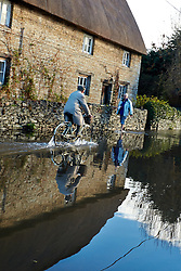 © Licensed to London News Pictures.  23/11/2012. OXFORD, UK. A man walks and another cycles through a flooded road in Kidlington, near Oxford. Overnight heavy rain has caused numerous floods. Photo credit :  Cliff Hide/LNP