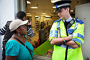 Local resident speaks with a police officer outside a looted and smashed up Tesco supermarket along London Road in Croydon. The day after rioting took place in Croydon in South London. Riots flared for a third night in a row, resulting in burnt out buildings, looted shops and general smashed up devastation.