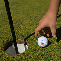 A youngster picks up his ball by the hole on a green at Big Sky Golf Course in Big Sky, Montana.