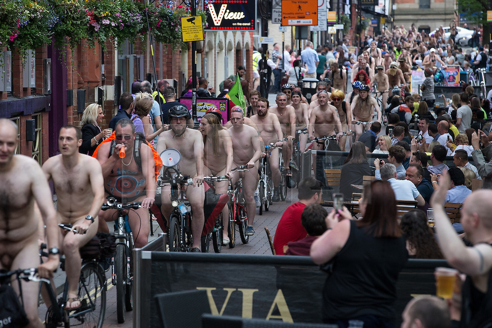 © Licensed to London News Pictures. 12/06/2015. Manchester, UK. The route of the ride passing through Canal Street in Manchester's Gay Village . Hundreds take part in the World Naked Bike Ride , which sees cyclists undress and cycle nude through Manchester City Centre . Photo credit: Joel Goodman/LNP