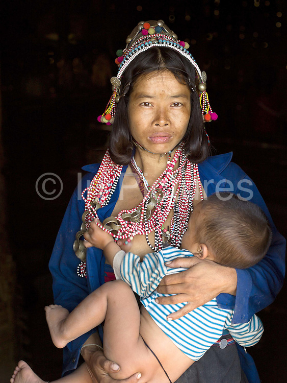 Portrait of an Akha Eupa ethnic minority woman breastfeeding her baby son in Ban Sa Nam Yang Pa village, Phongsaly province, Lao PDR. One of the most ethnically diverse countries in Southeast Asia, Laos has 49 officially recognised ethnic groups although there are many more self-identified and sub groups. These groups are distinguished by their own customs, beliefs and rituals. Details down to the embroidery on a shirt, the colour of the trim and the type of skirt all help signify the wearer's ethnic and clan affiliations.