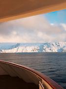 Snowy, frozen landscapes seen from a boat at sea in Finnmark region, northern Norway