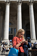 A lady checks messages beneath the neo-classical pillars of Royal Exchange in the City of London - the capitals financial centre aka The Square Mile, on 27th September 2018, in London, England.