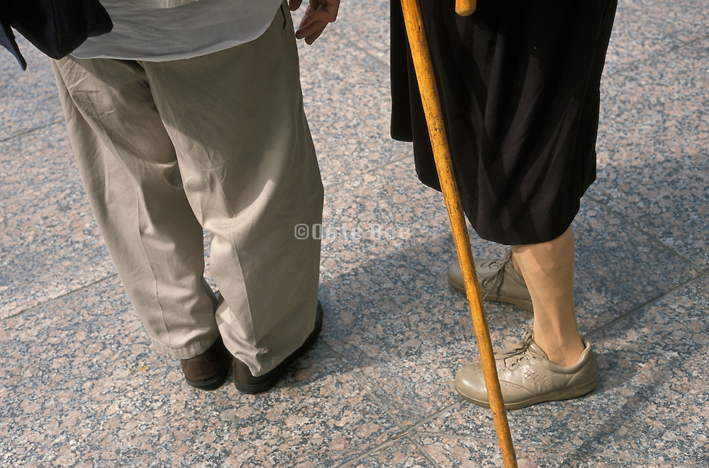 Close up of elderly man and an elderly woman with a cane